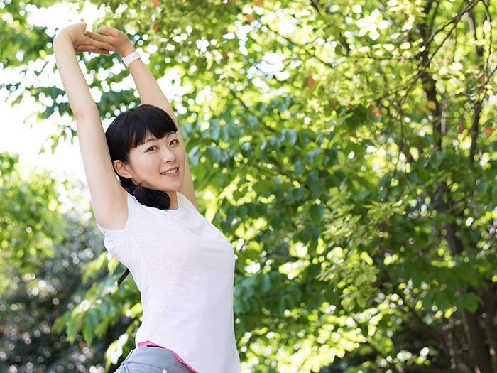 自然の中で気持ちよく背のびをしている女性