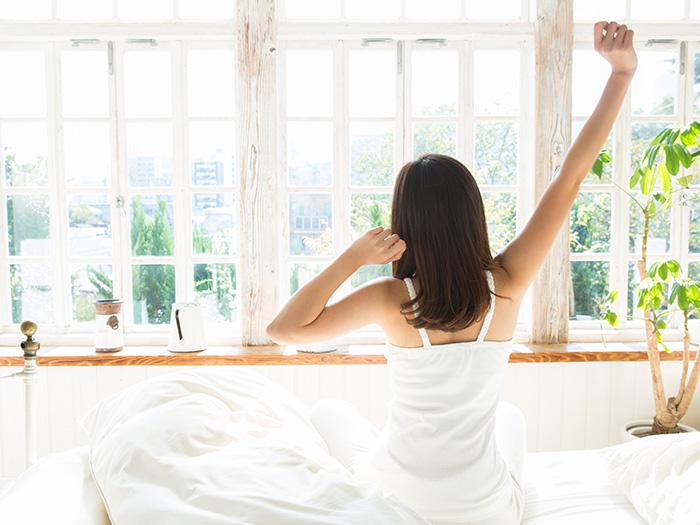 ベッドの上でのびをしている女性の後姿